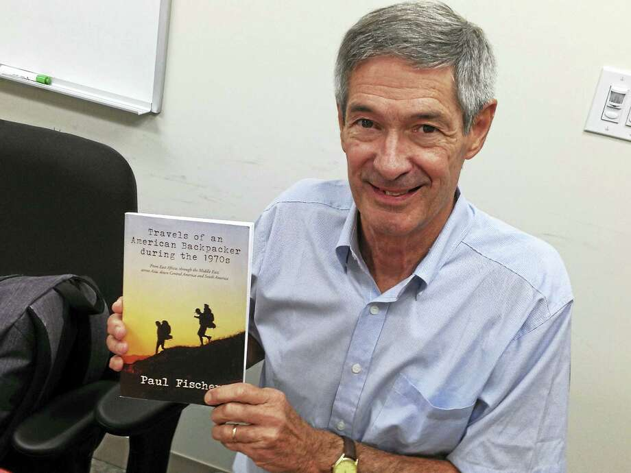 "Expatriate native West Havener Paul Fischer, now living in Chile, with a copy of his new book, ""Travels of an American Backpacking During the 1970s."" Photo: Mark Zaretsky — New Haven Register"