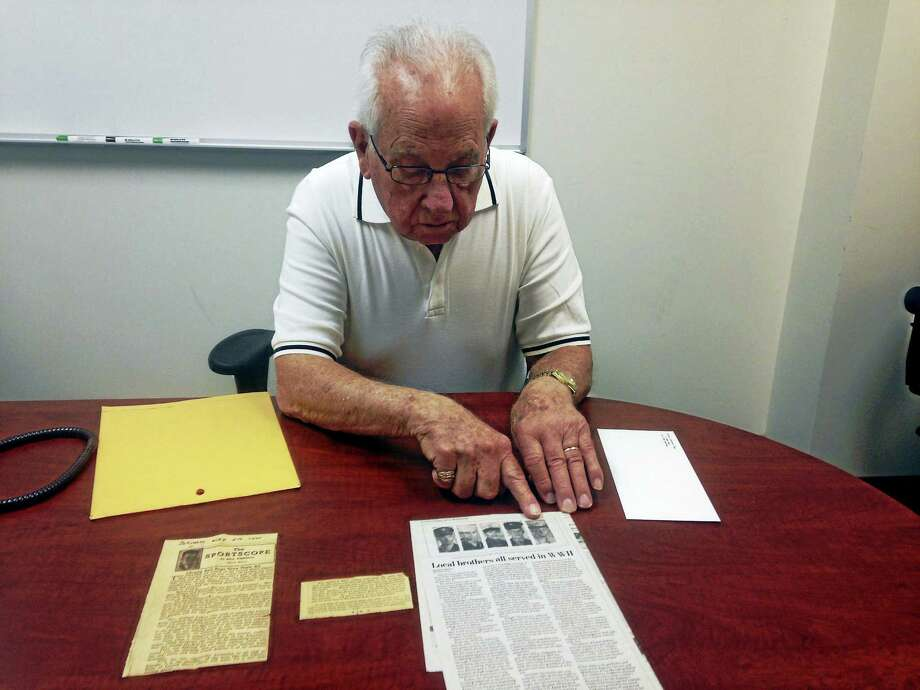 Robert C. Ruby looks over an article in the Journal Courier written based on a letter he submitted while he was in the Army during WWII. Photo: Juliemar Ortiz — New Haven Register