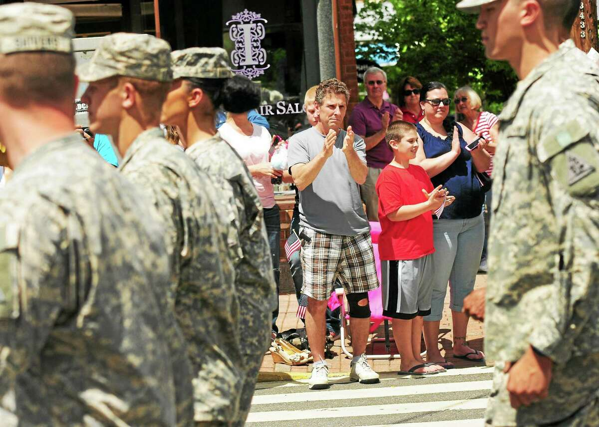 John Gagliardi of Seymour, Andon Salva, 10, of Seymour, and his mother, Jaemie Altieri, of Seymour, left to right center, clap as a contingent from the Connecticut National Guard marches up Main Street during the annual Town of Seymour, Connecticut Memorial Day Parade Sunday, May 25, 2014.