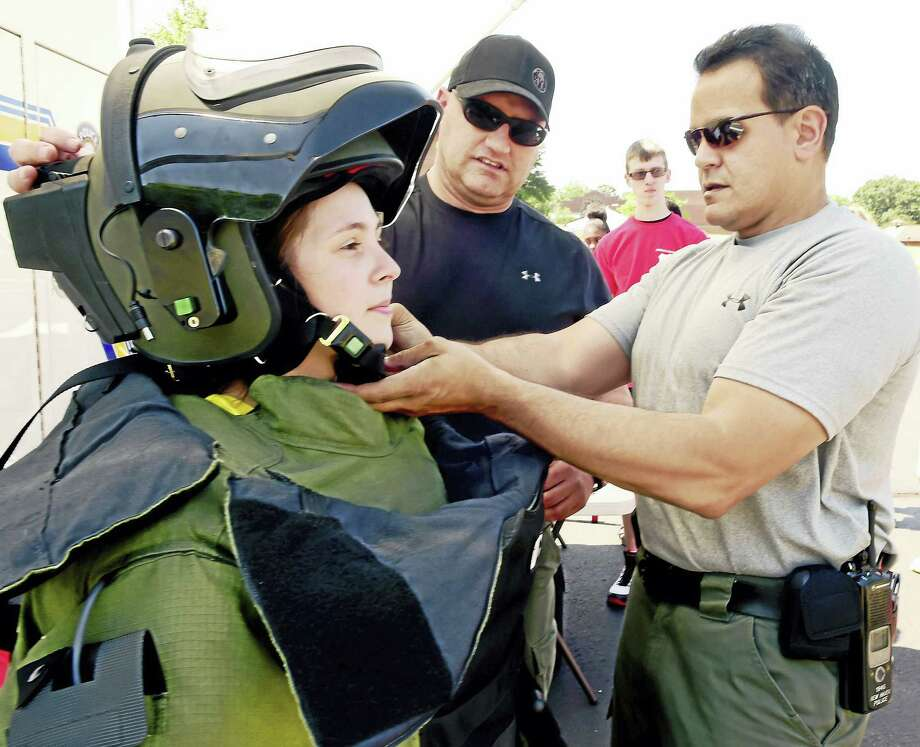 Kaitlyn Spann, 17, of Bristol, left, is helped into a Eng EOD 9 Bomb Suit Wednesday by New Haven Police Department Bomb Squad members Ed Dunford, center, and Juan Ingles, right, during the seventh annual Criminal Justice Camp for high school juniors and seniors hosted by Albertus Magnus College in New Haven. Photo: Peter Hvizdak — New Haven Register   / ©2016 Peter Hvizdak