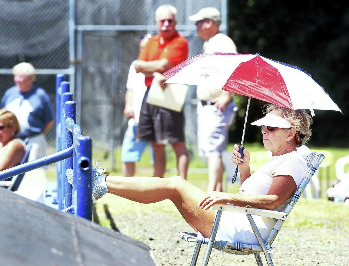 Joanne Backert of Monroe shields herself from the sun while watching the West Haven Twilight League All-Star game at Quigley Stadium in West Haven Saturday.