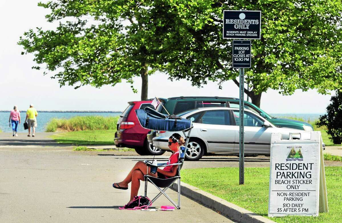 Alyssa Talamelli of West Haven, right, a City of West Haven constable, monitors resident parking beach stickers at the parking lot at the Bradley Point on Ocean Avenue in West Haven in July 2014.