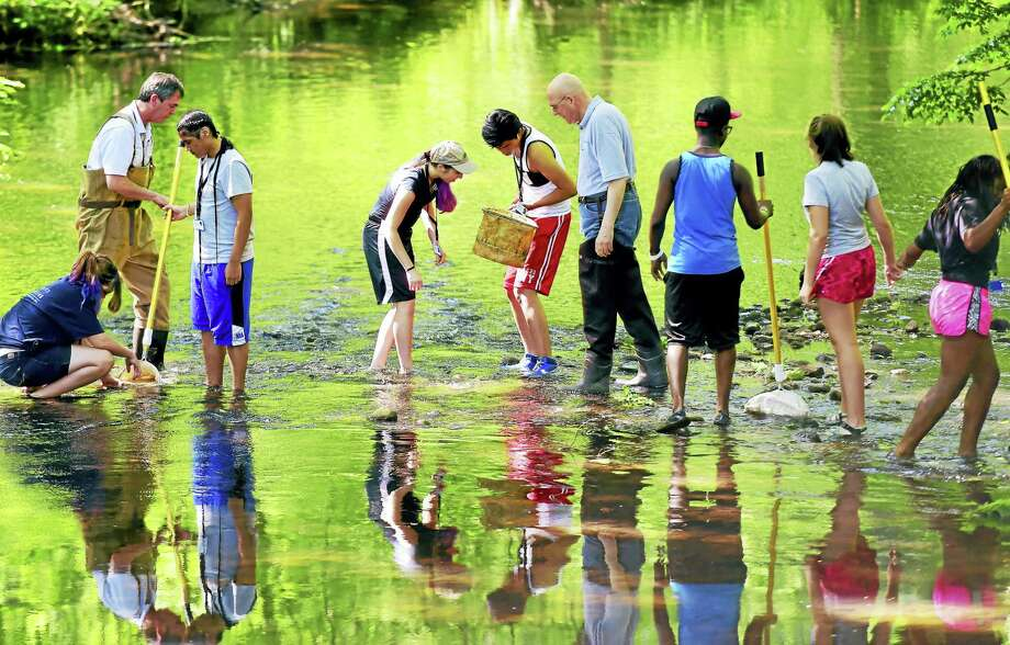 John Triana of the South Central Connecticut Regional Water Authority, second from left, and Larry L. Bingaman, president and CEO of the Regional Water Authority, fourth from right, assist in the search for macroinvertebrates on a field trip to the Mill River in Hamden Wednesday with Environmental Career Summer Camp students. The summer camp is sponsored by the Regional Water Authority and the Common Grounds school in New Haven. Photo: Peter Hvizdak — New Haven Register   / ©2016 Peter Hvizdak
