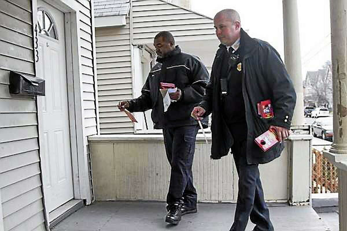 Then-New Haven Fire Department Assistant Chief Patrick Egan and Firefighter Michael Neal hang recruitment fliers on doors in the Hill Fire District in January 2013.