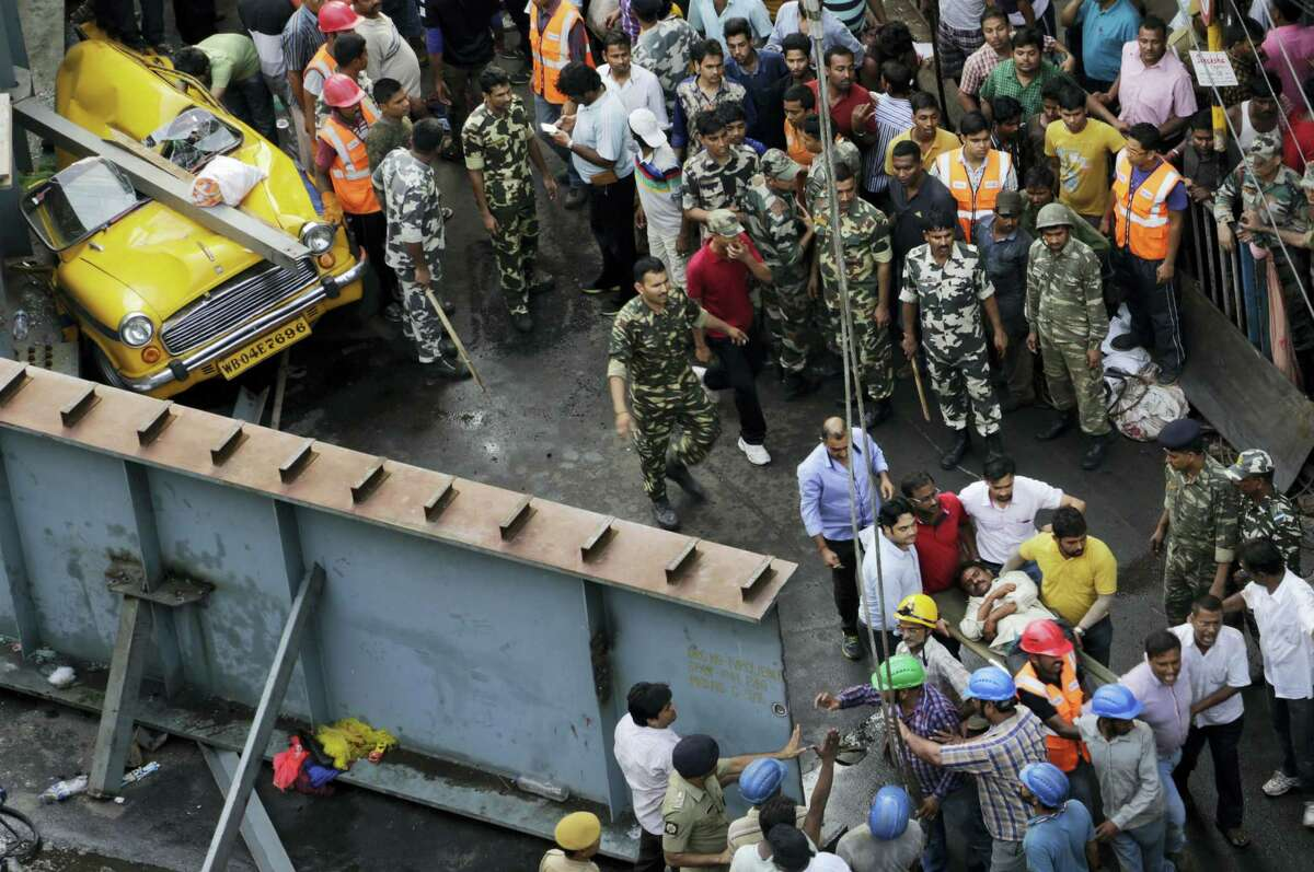 Rescue workers take an injured man for medical treatment after retrieving him from underneath a partially collapsed overpass in Kolkata, India,Thursday, March 31, 2016. A long section of a road overpass under construction collapsed Wednesday in a crowded Kolkata neighborhood, with tons of concrete and steel slamming into midday traffic, killing several and injuring many.