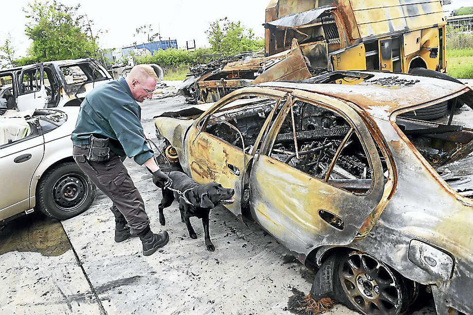 Detective Sgt. David Sutton of the Vermont State Police handles Biscuit, an accelerant detection canine, as she sniffs around a burned out car Tuesday for traces of accelerant during quarterly training at the New Haven Regional Fire Academy in New Haven. The car was used earlier in the day for fire investigation training. Photo: Photo By Arnold Gold — New Haven Register