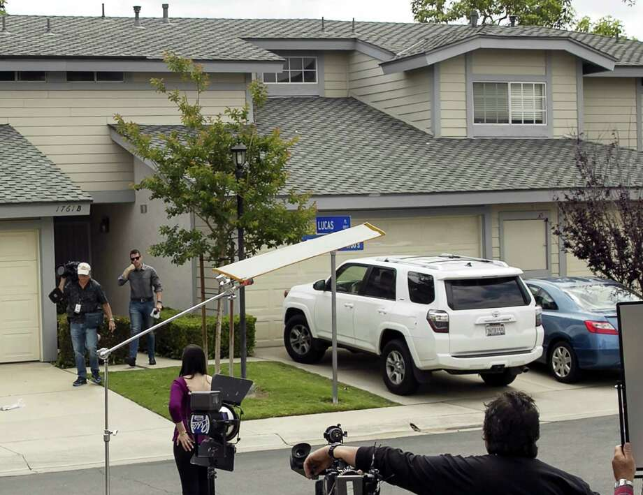 Members of the media stand outside the home of Syed Raheel Farook, the elder brother of San Bernardino gunman Syed Rizwan Farook, after the FBI served a warrant to the location, in Corona, Calif., Thursday, April 28, 2016.  Syed Raheel Farook was arrested with two others Thursday in what prosecutors say was a marriage scheme to fraudulently allow one of them to remain in the United States. Photo: AP Photo — Damian Dovarganes / Copyright 2016 The Associated Press. All rights reserved. This material may not be published, broadcast, rewritten or redistributed without permission.