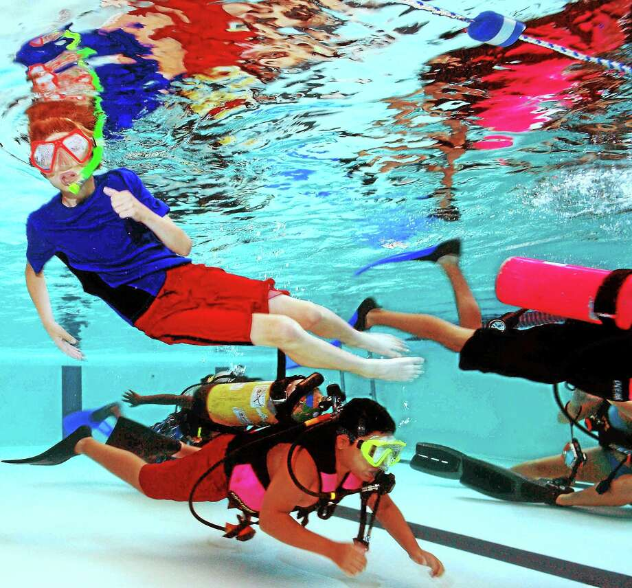 Scuba diving teens immerse themselves in the underwater weightless environment of the Wilbur Cross High School pool as they learn the basics of breathing under water during a session of the Eco Adventure Extreme Camp in 2014. Photo: Peter Hvizdak — New Haven Register    / ©Peter Hvizdak /  New Haven Register