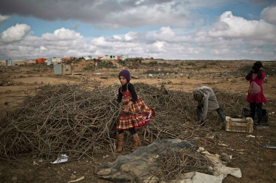 In this file photo, Syrian refugee girls collect wood to be used for heating at an informal tented settlement near the Syrian border on the outskirts of Mafraq, Jordan, Saturday, Jan. 23, 2016. A suicide bomber killed six Jordanian security troops on that border Tuesday, June 21, 2016, and wounded 14 people. Photo: AP Photo/Muhammed Muheisen    / AP