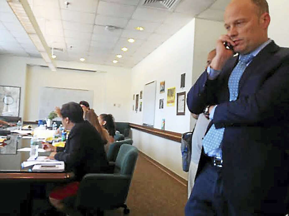 Superintendent of Schools Garth Harries calls to the city clerk's office to confirm when he sent the notice for a meeting Monday. Photo: Brian Zahn — New Haven Register