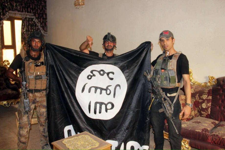 In this image taken by an Iraqi Counterterrorism Service photographer on June 19, 2016, soldiers pose with an Islamic State militant flag in Fallujah, Iraq after forces re-took the city center after two years of IS control. Photo: Iraq Counterterrorism Service Via AP   / Iraq Counterterrorism Sevice
