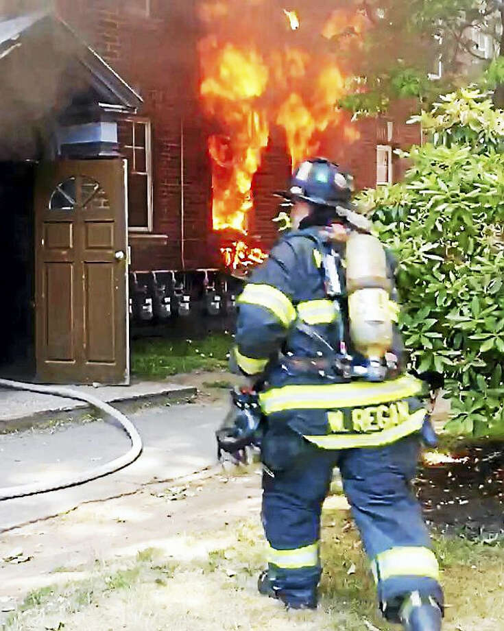 New Haven Firefighter William Regan helps battle a two-alarm blaze at 202 Sherman Ave. early Tuesday afternoon. No one was hurt in the fire but people were displaced from 10 apartment units. Photo: Photo Courtesy Of The New Haven Fire Department