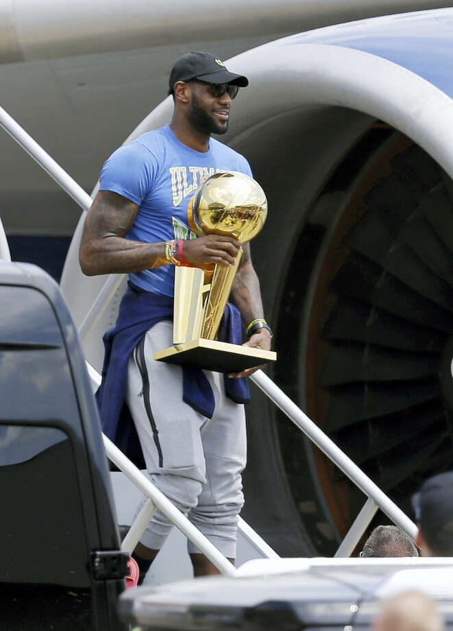 Cleveland Cavaliers' LeBron James carries The Larry O'Brien NBA Championship Trophy after arriving in Cleveland on June 20, 2016. Photo: AP Photo/Tony Dejak   / Copyright 2016 The Associated Press. All rights reserved. This material may not be published, broadcast, rewritten or redistribu