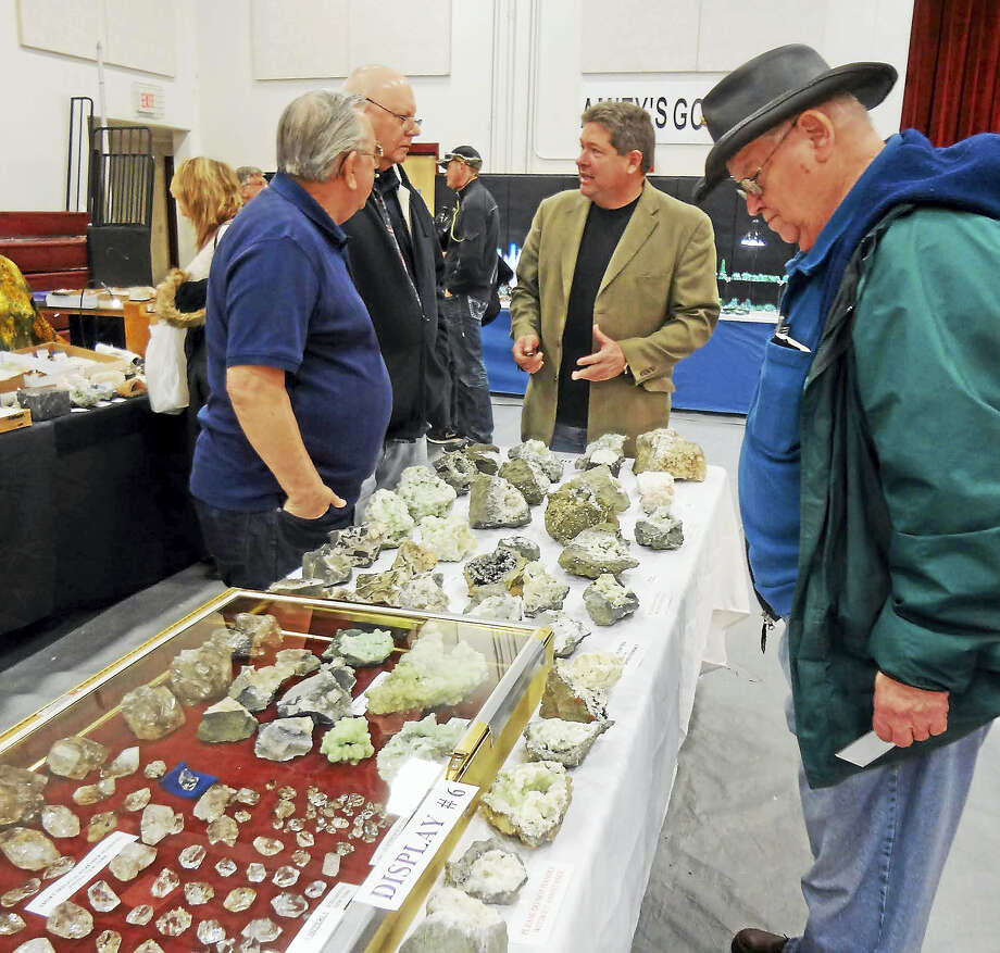 At last year's New Haven Mineral Club show, Jim Sipperly, center, talks about his Prehnite specimens. In the case are Herkimer diamonds (quartz), and superb Prehnite specimens. Photo: Photo Courtesy Of Art Doyle
