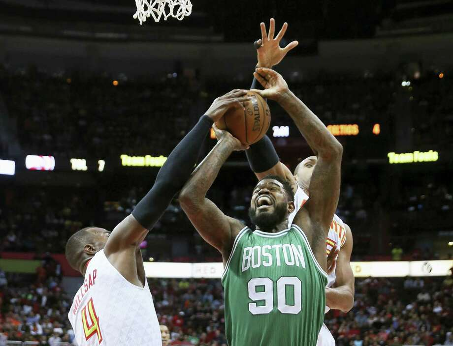 Celtics forward Amir Johnson (90) has his shot blocked by Hawks forward Paul Millsap (4) as center Al Horford defends during the first half on Tuesday. Photo: John Bazemore — The Associated Press   / Copyright 2016 The Associated Press. All rights reserved. This material may not be published, broadcast, rewritten or redistributed without permission.