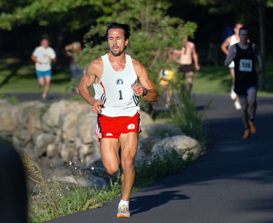 "Anatolie Vartosu of Stamford was the first place finisher for the men in the the ""Cook Your Buns"" 3-mile race at Greenwich Point, Friday evening, June 11, 2010. Photo: Bob Luckey / Greenwich Time"