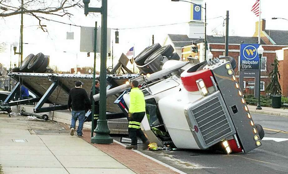 Part of Main Street in East Haven was shut down for hours Tuesday morning after a tractor-trailer rolled over and spilled a load of concrete slabs onto the street and sidewalk. The driver suffered only minor injuries, police confirmed. Photo: Wes Duplantier — New Haven Register
