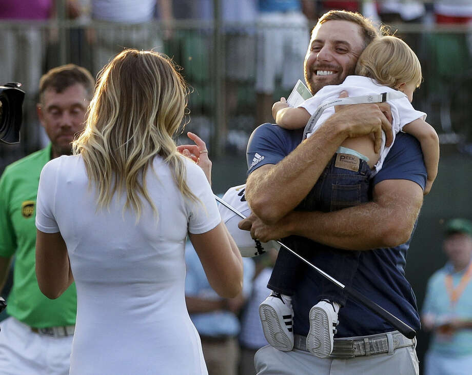 Dustin Johnson, right, greets his fiancé Paulina Gretzky as he holds their son Tatum Gretzky at the U.S. Open at Oakmont Country Club on Sunday. Photo: John Minchillo — The Associated Press   / AP