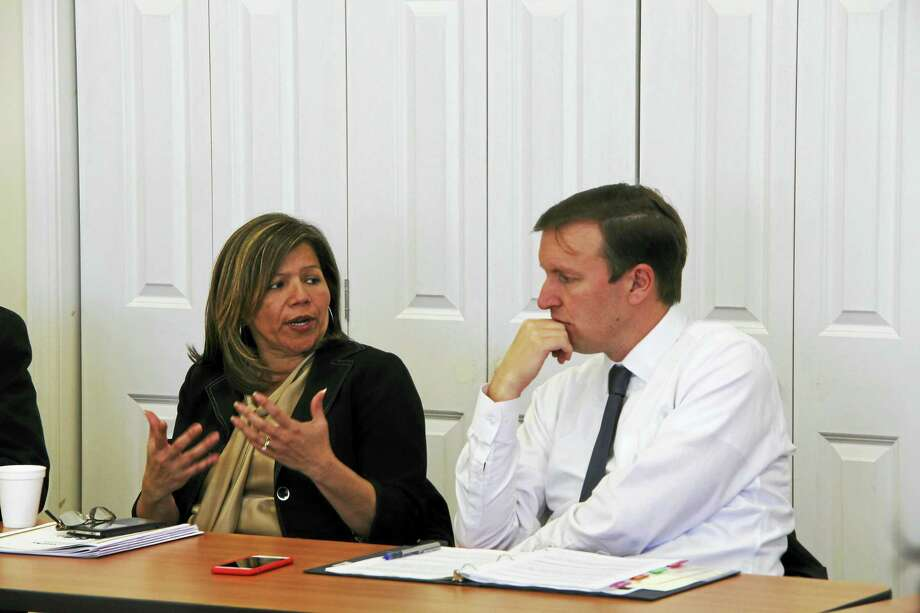 Seila Mosquera-Bruno, executive director of NeighborWorks New Horizons, talks with U.S. Sen. Chris Murphy (right), about financial struggles for families needing to pay for lead abatement in their homes. Photo: Anna Bisaro — New Haven Register