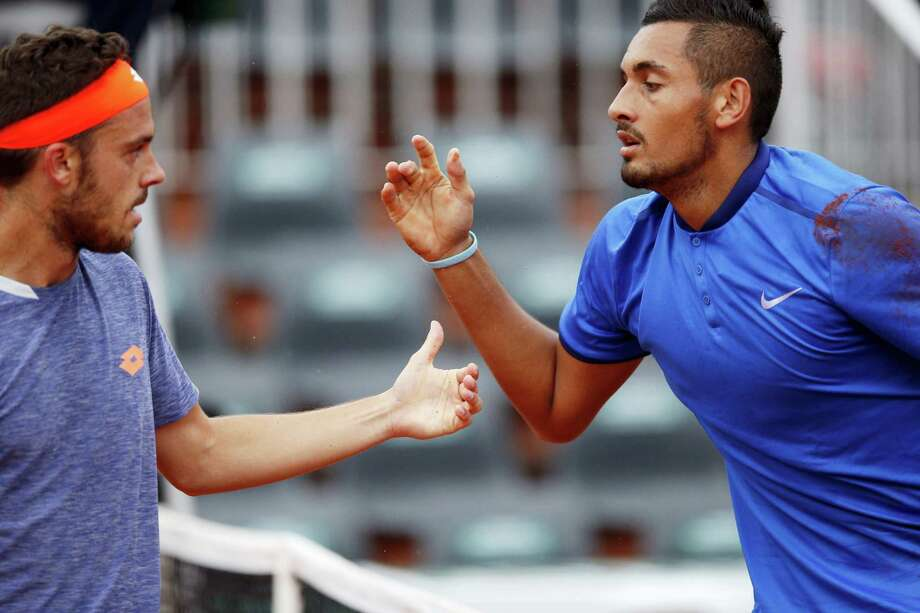 Nick Kyrgios, right, and Marco Checchinato gesture during their first-round match at the French Open on Sunday. Photo: Christophe Ena — The Associated Press   / AP