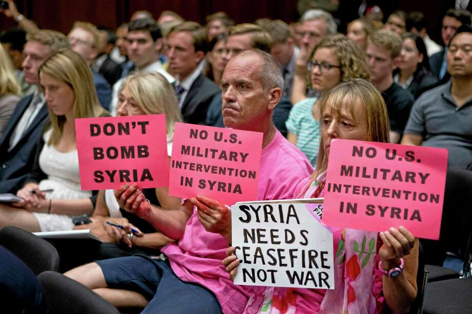 CODEPINK co-founder Medea Benjamin, right, and other protestors hold up signs in the hearing room on Capitol Hill in Washington in this archive photograph. Photo: File Photo   / AP