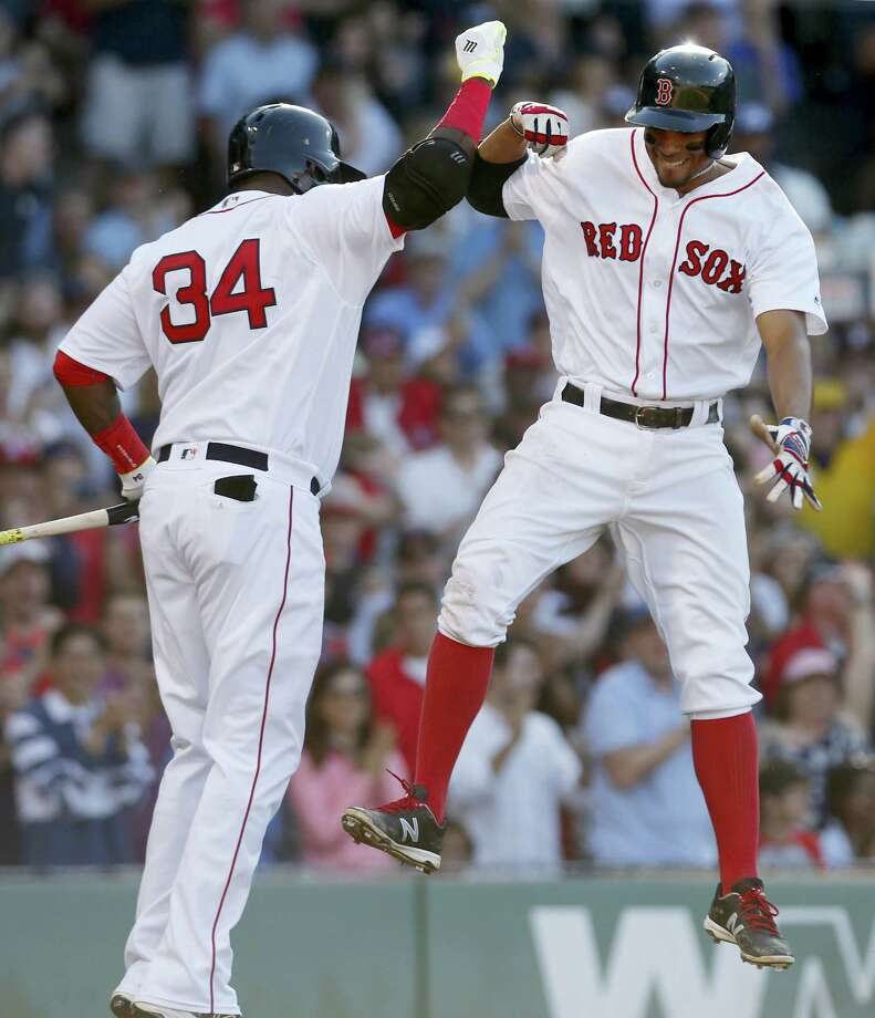 Xander Bogaerts, right, leaps to celebrate with David Ortiz after hitting a home run during the fifth inning on Saturday. Photo: Mary Schwalm — The Associated Press   / FR158029 AP