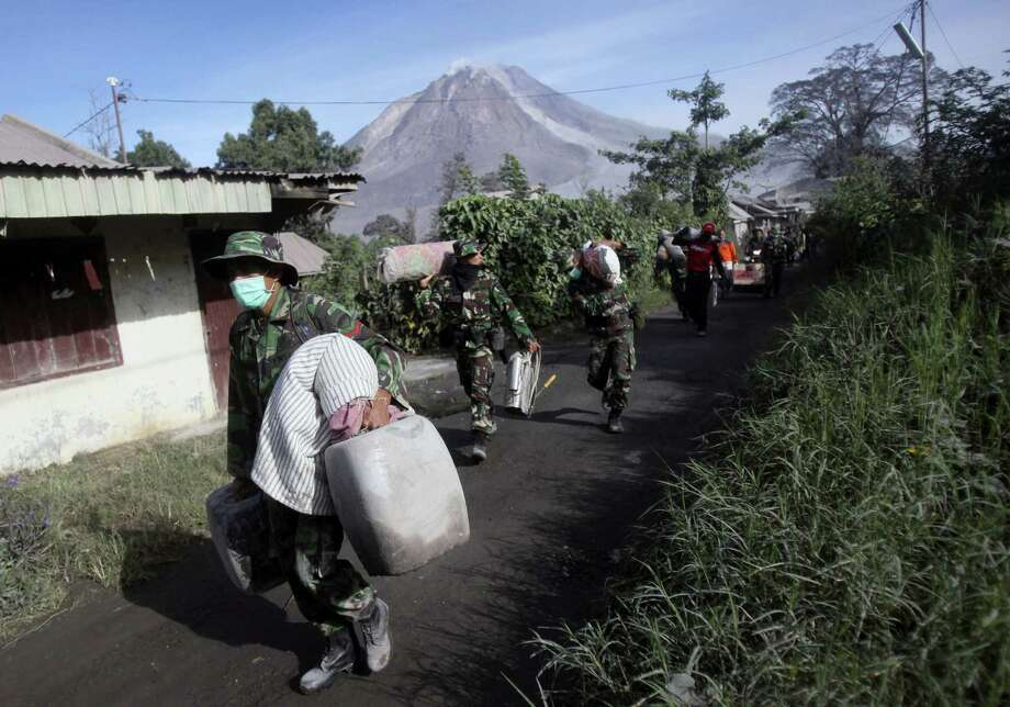Indonesian soldiers carry people's belongings during an evacuation following the eruption of Mount Sinabung in Gamber village, North Sumatra, Indonesia on May 22, 2016. The volcano in western Indonesian unleashed hot clouds of ash on Saturday, killing several villagers, officals said. Photo: AP Photo/Binsar Bakkara   / Copyright 2016 The Associated Press. All rights reserved. This material may not be published, broadcast, rewritten or redistribu