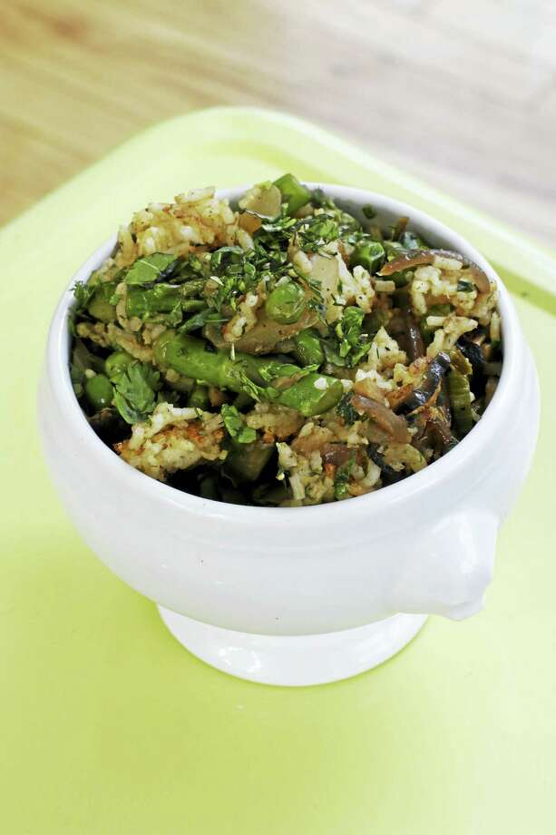 The combination of rice packed with spiced fennel, onions and garlic cooked slowly until soft and finished with still-crisp asparagus and peas makes for a perfect spring dish. Photo: J.M. Hirsch — The Associated Press   / AP