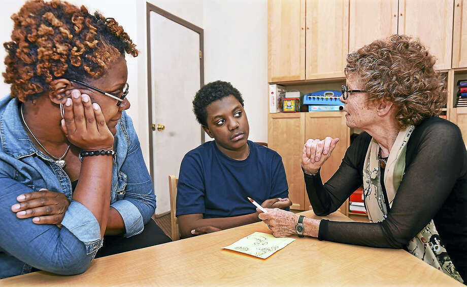 Speech and Language pathologist Alida Engel works with 11-year old Troy Wylie, who has been a student of Engel at the Center for Speech & Learning on Edgewood Avenue in New Haven since he was 3 years old. Troy's mother, Tracey Foskey of New Haven, at left, started a support group for parents of autism. Photo: Catherine Avalone — New Haven Register      / New Haven RegisterThe Middletown Press