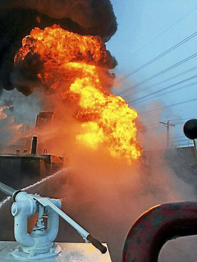 New Haven firefighters battled a fire in a piece of excavation equipment Monday night at the Port of New Haven on Waterfront Street. A firefighter suffered a minor neck injury in the blaze. Photo: Photo Courtesy Of The New Haven Fire Department