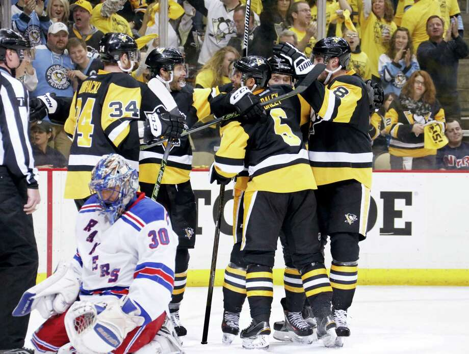 Rangers goalie Henrik Lundqvist kneels on the ice as members of the Penguins' celebrate a second-period goal on Saturday. Photo: Gene J. Puskar — The Associated Press   / Copyright 2016 The Associated Press. All rights reserved. This material may not be published, broadcast, rewritten or redistributed without permission.