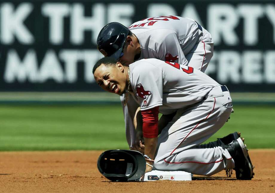 Mookie Betts grimaces after he was hit by an errant throw from Astros pitcher Mike Fiers. Photo: Pat Sullivan — The Associated Press   / Copyright 2016 The Associated Press. All rights reserved. This material may not be published, broadcast, rewritten or redistributed without permission.