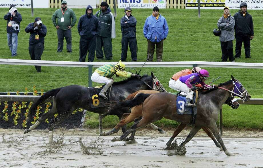 Homeboykris (3), ridden by Horacio Karamanos, moves to the finish in the first race of the day on a muddy track ahead of the 141st Preakness Stakes horse race at Pimlico Race Course, Saturday, May 21, 2016, in Baltimore. Photo: AP Photo/Garry Jones    / FRE1234 AP