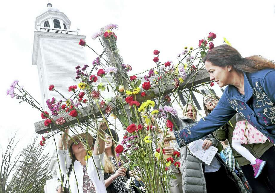 Arnold Gold — New Haven Register  Dana Shaffer (right) of Orange joins other parishioners in placing flowers on a cross in front of Orange Congregational Church after the Easter Service on 3/27/2016. Photo: Journal Register Co.