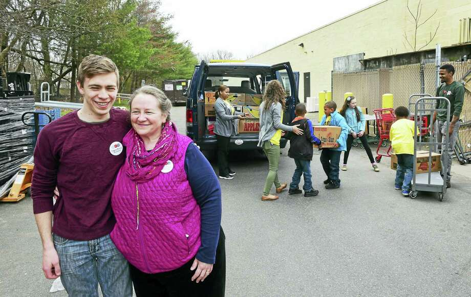 Caleb MartinMooney, 19,  and his mother Lori Martin, both of New Haven, who represent Community Plates Greater New Haven, pick up food at Trader Joe's food market in Orange recently with the assistance of ACES Mill Road School in North Haven. Community Plates directly transfers fresh, usable food that would have otherwise been thrown away from restaurants, markets and other food industry sources to food-insecure families, according to the organization's website. Photo: (Peter Hvizdak - New Haven Register)   / ©2016 Peter Hvizdak