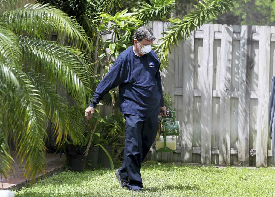 In this photo taken April 12, 2016, Giraldo Carratala, an inspector with the Miami- Dade County, Fla. mosquito control unit, sprays pesticide in the yard of a home in Miami, Fla. Photo: AP Photo — Lynne Sladky / Copyright 2016 The Associated Press. All rights reserved. This material may not be published, broadcast, rewritten or redistribu