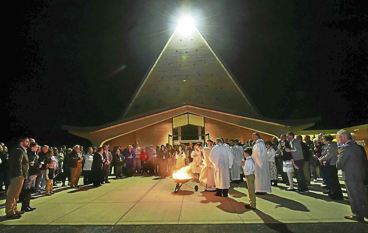(Catherine Avalone - New Haven Register) Rev. Robert L. Turner, the Pastor of the Parish Community of St. Ambrose in North Branford prepares to light the Paschal candle at the Holy Saturday Easter Vigil at St. Augustine Church on Caputo Road in North Branford, Saturday, March 26, 2016. St. Augustine's and St. Monica Church in Northford merged forming St. Ambrose, which is the first merger in the Archdiocese of Hartford.