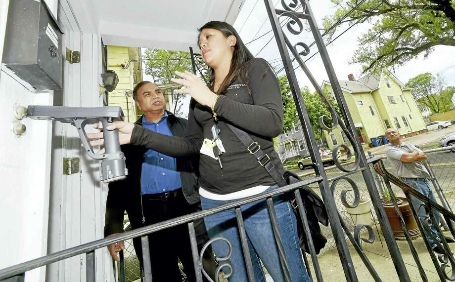 Glenda Wolfe, a city Health Department lead poison inspector, center, demonstrates the use of an XRF lead paint analysis machine on the outside of a two-family rental house on Blatchley Avenue in New Haven owned by landlord Paul Chadha, left. William Diaz, at far right, is a tenant there. Photo: Peter Hvizdak — New Haven Register   / ©2016 Peter Hvizdak