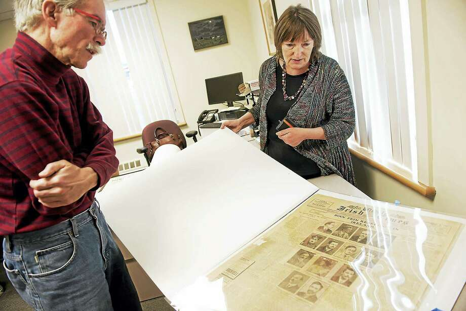 "Quinnipiac University history professors Michael Chiarappa and Christine Kinealy, director of Ireland's Great Hunger Institute, look over an old edition of the Weekly Irish Times, which was published in Dublin in the wake of the Easter Rising of 1916. They are the curators of the exhibition, ""The Seed of the People: 1916 Remembered,"" which ends Sept. 30. Photo: Autumn Driscoll/Quinnipiac University   / (Autumn Driscoll / Quinnipiac University)"