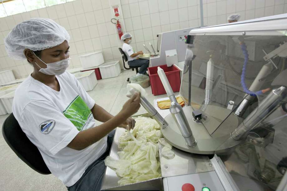 A worker checks rubber condoms at the government-run Natex factory in Xapuri, in Brazil's Amazon. The International Olympic Committee confirmed that three times more condoms will be distributed during the Rio de Janeiro Olympics in 2016 than at the London games four years prior. Photo: The Associated Press File Photo   / AP