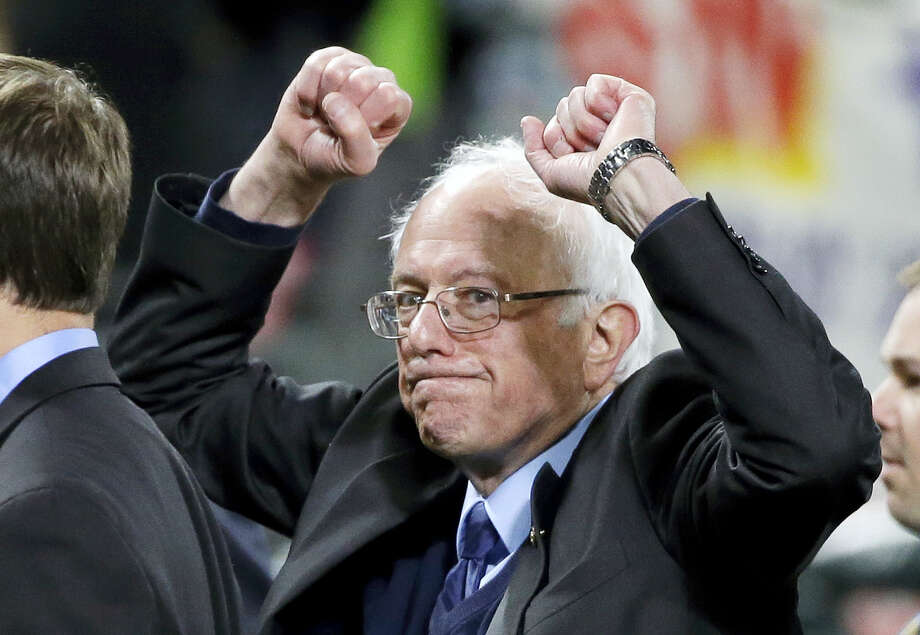 Democratic presidential candidate Sen. Bernie Sanders, I-Vt., pumps his fists as he leaves the field after speaking at a rally Friday, March 25, 2016, in Seattle. Photo: AP Photo — Elaine Thompson / Copyright 2016 The Associated Press. All rights reserved. This material may not be published, broadcast, rewritten or redistributed without permission.