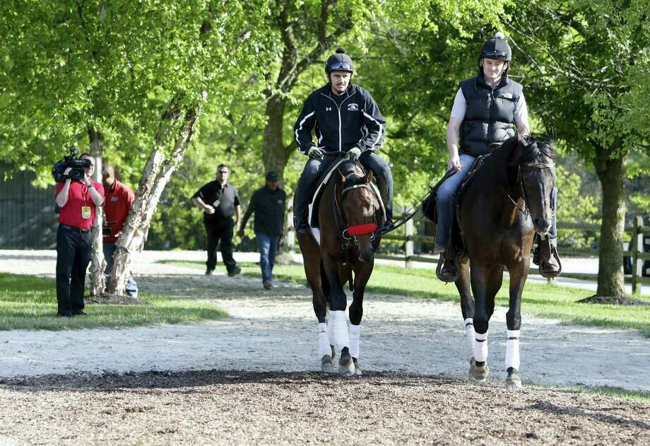 Nyquist, left, ridden by exercise rider Jonny Garcia, walks to the barns with assistant trainer Jack Sisterson at Pimlico Race Course on Friday. Photo: Garry Jones — The Associated Press   / FRE1234 AP