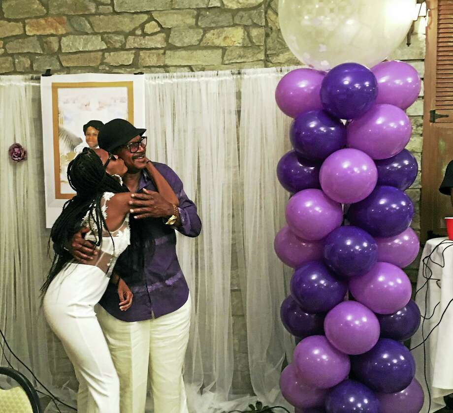 Quanisha Cole, Jajuana Cole's sister, gives her grandfather Frank Whitfield a kiss at a party honoring the life of Jajuana Friday in New Haven. Photo: ED STANNARD — NEW HAVEN REGISTER