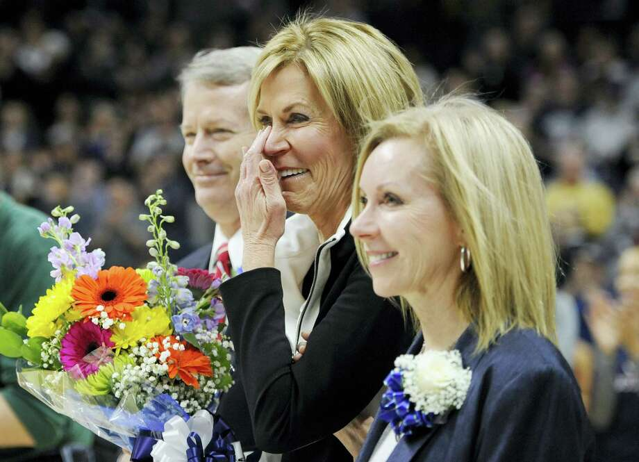 UConn associate head coach Chris Dailey wipes a tear away as she stands with her family during a surprise unveiling of her name on the UConn Huskies of Honor wall on Saturday. Photo: Jessica Hill — The Associated Press   / FR125654 AP