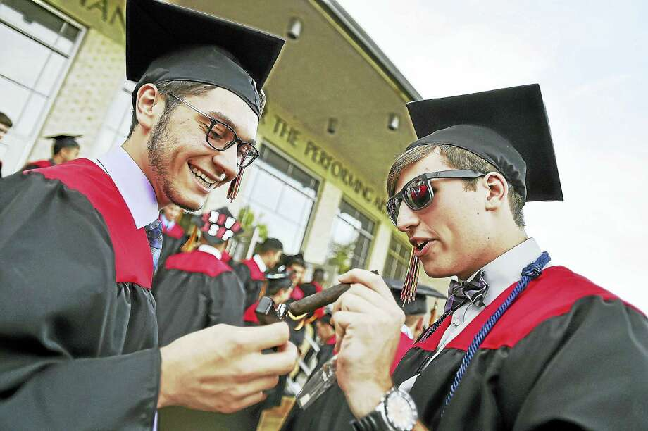Joseph Fraulo and Mike Iozzo light up cigars following Platt Technical High School commencement exercises Wednesday at the John Lyman Center for the Performing Arts at Southern Connecticut State University in New Haven. Photo: Catherine Avalone — New Haven Register