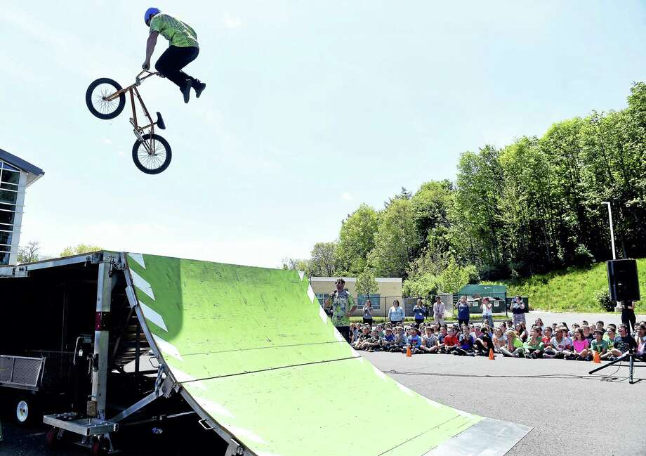 Zane Bradley of Dialed Action Sports Team performs a stunt on his BMX bicycle for students at Chatfield-LoPresti Elementary School in Seymour Friday. Photo: Arnold Gold — New Haven Register