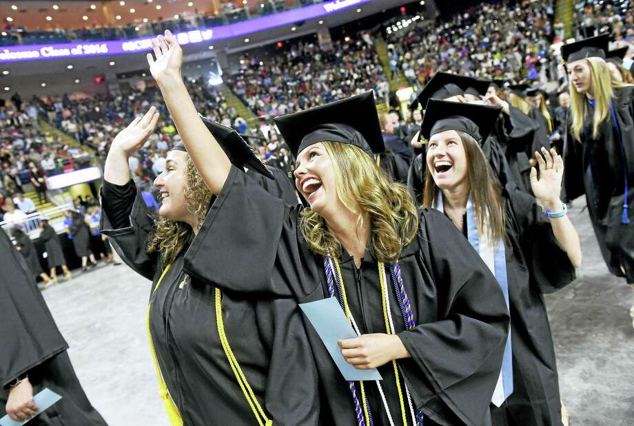From left, Jillian DiTota, Rebecca Morrell and Eliza Doane wave as they view themselves on a monitor during Southern Connecticut State University's undergraduate commencement Friday at Webster Bank Arena in Bridgeport. Photo: Arnold Gold — New Haven Register