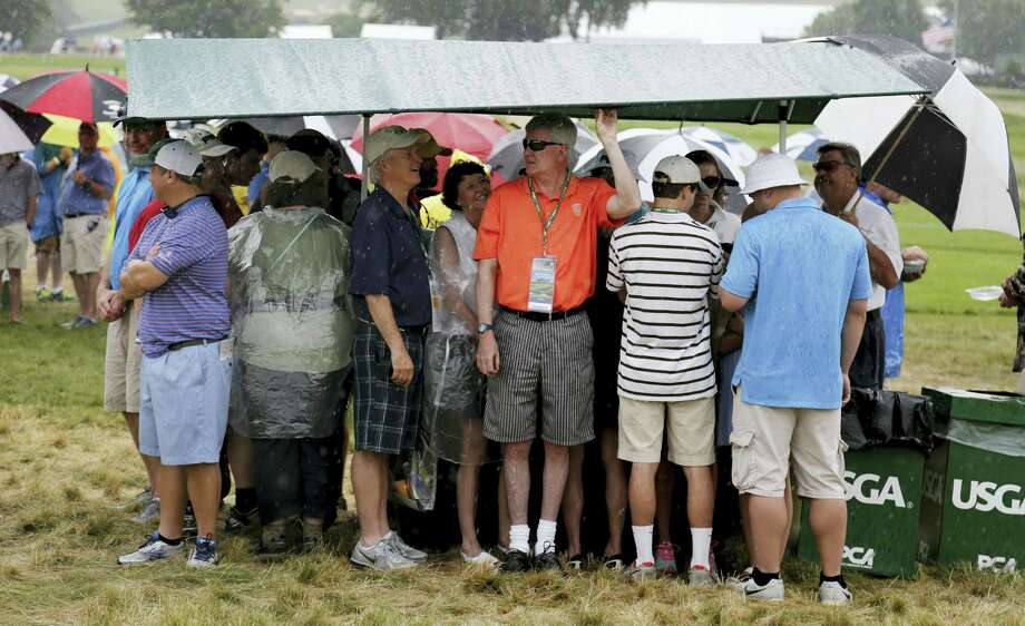 Fans take shelter from the rain after play was suspended during the first round of the U.S. Open golf championship at Oakmont Country Club on June 16, 2016 in Oakmont, Pa. Photo: AP Photo/Gene J. Puskar   / AP