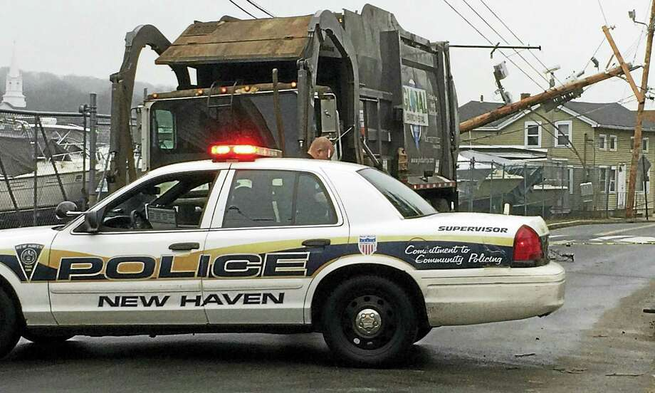 Front Street was shut down Friday morning near Pine Street and the Waucoma Yacht Club after a garbage truck snagged on utility wires and snapped a pole in the half. The truck driver was unhurt but United Illuminating had to close the road to replace the pole. Photo: (Wes Duplantier/New Haven Register)