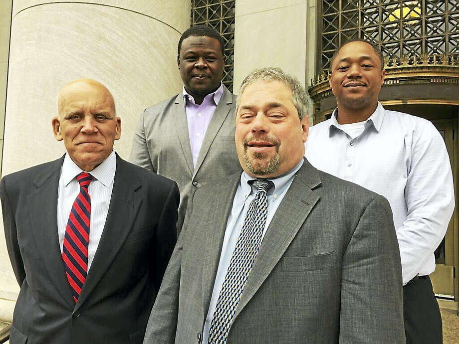 CONTRIBUTED PHOTO  Plaintiffs and attorneys in a racial discrimination case against Safety Marking pose outside of New Haven District Court. Pictured from left, front, attorneys Paul Thomas and Lewis Chimes, and back, plaintiffs Yosif Bakhit and Kiyada Miles. Photo: Journal Register Co.